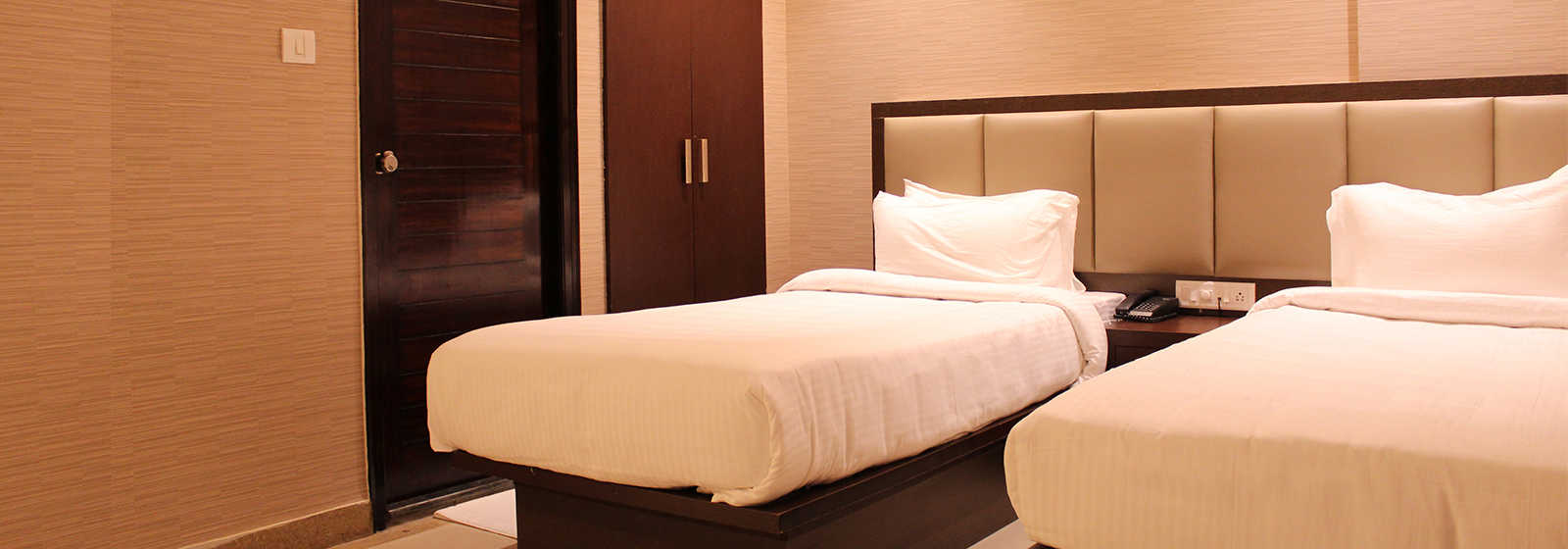 Super Deluxe room with twin beds, wardrobe and an attached bathroom at The Byke's Bangalore hotel.