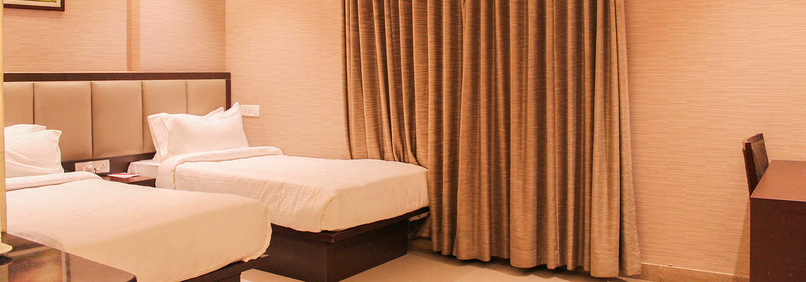 Super Deluxe Twin bedroom with white linen, study table, long curtains and AC at The Byke Signature hotel in Bangalore.