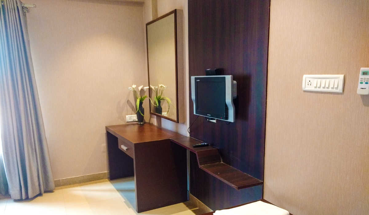 A wooden study table with a flower vase on it and TV in Super Deluxe Room at The Byke Signature hotel in Bangalore.